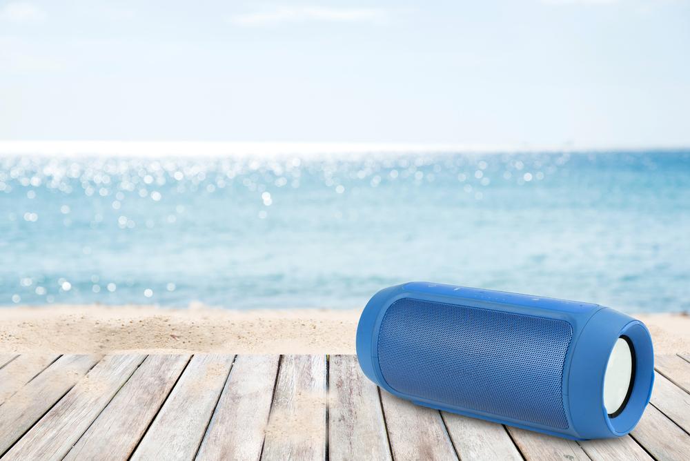 A blue Bluetooth speaker sitting on a wood platform at the beach