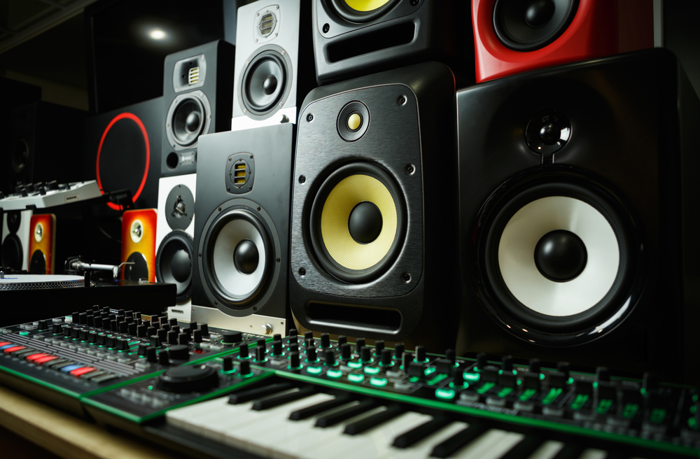 a variety of different bookshelf speakers stacked in front of a sound mixer