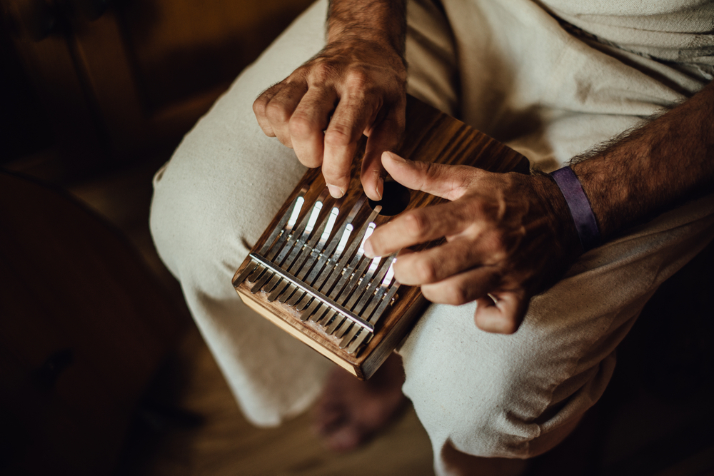 an older gentleman plays the kalimba while seated