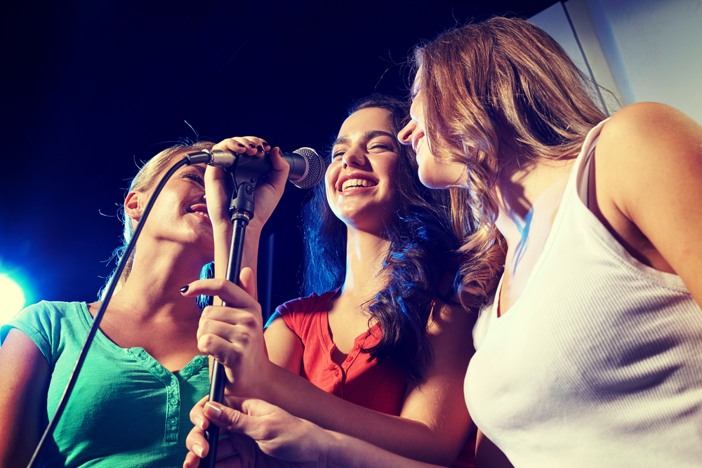 women on stage sing into a mic